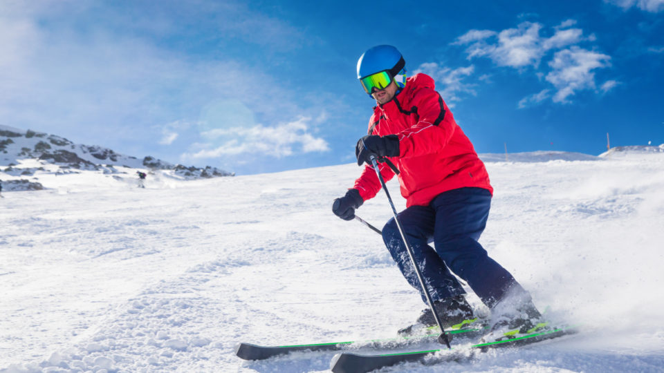 Man skiing on the prepared slope with fresh new powder snow in Tyrolian Alps, Zillertal, Austria