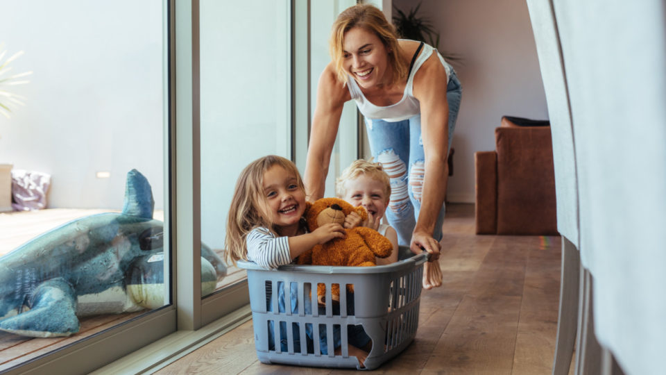 Happy young mother pushing children sitting in laundry basket. Mother and children playing at home.
