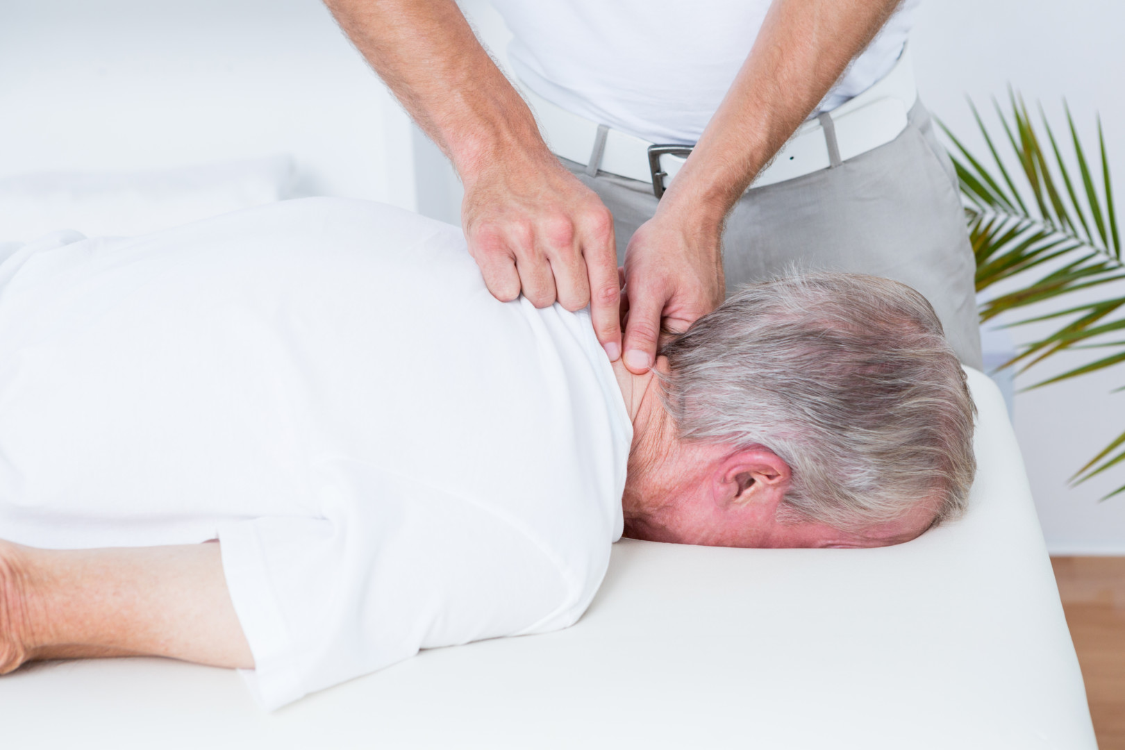 Physiotherapist doing neck massage to his patient in medical office